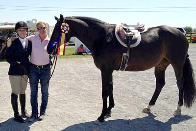 A horse and its trainer win a ribbon
