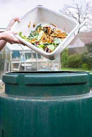 A woman pours winter vegetables into a composting bin