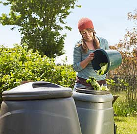 A woman dumps old cabbage leaves into a composter.