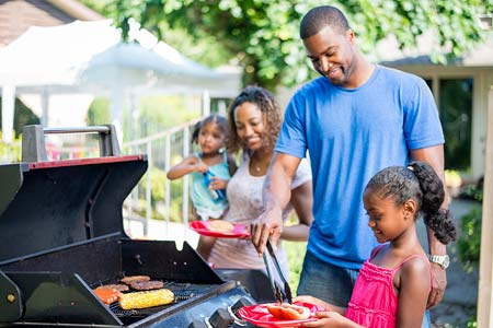 A family safely uses a gas grill