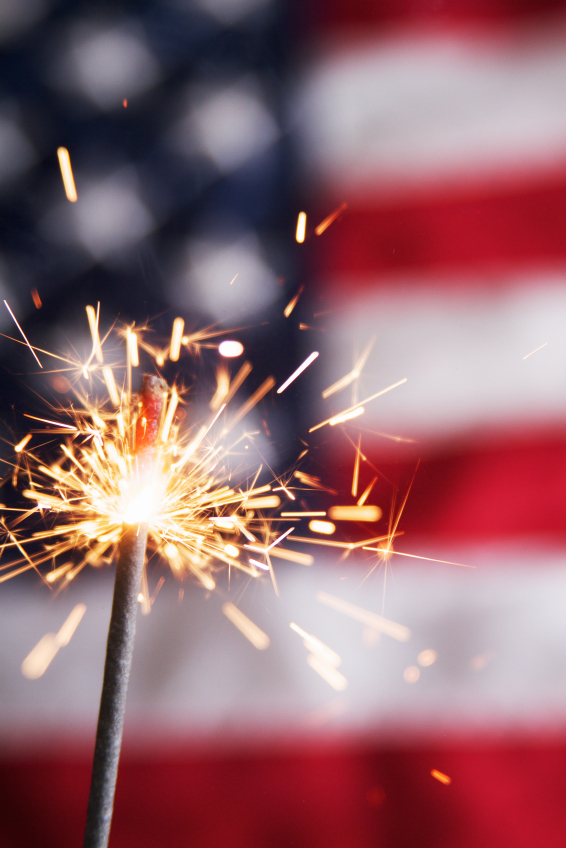 A sparkler glows in front of an American flag